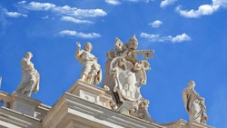 Zoom detail photo of sculptures on top of Saint Peter  basilica in Vatican City, Rome, Italy