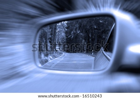 Zoom effect on exterior rear view mirror with rural woodlands
