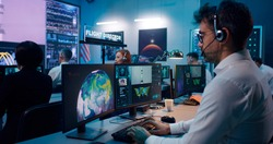 Zoom in view of mature man with headset using computer while launching spacecraft with astronaut remotely with team in flight control center