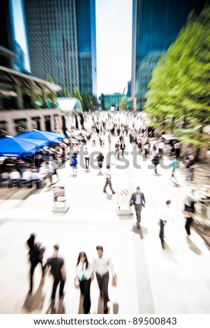 Zoom on business people rushing around at Canary Wharf, London. Motion blur.