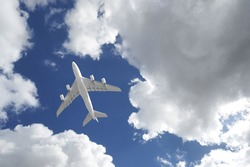 Zoom photo from ground level of passenger plane flying above deep blue cloudy sky