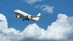 Zoom photo of passenger plane flying above deep blue cloudy sky