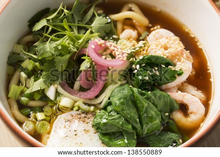 Zoomed bowl with broth and boiled shrimp between sticks