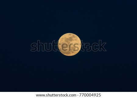 Stock Photo Zoomed in rising yellow moon in the deep blue dark sky.