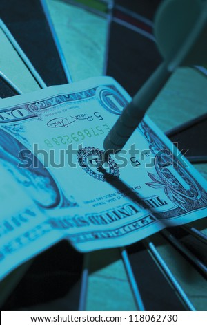 zoomed in shot of an american dollar bill pinned down on a dartboard in blue light