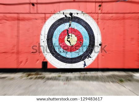 Zooming onto a colorful bulls eye target on a red concrete wall.