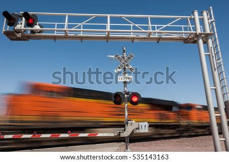 Zooming train engine speeding past railroad crossing