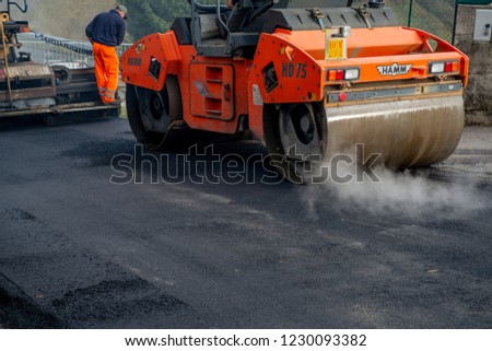 zorzone Italy November 14th 2018:workers at work to redo the road surface #1230093382