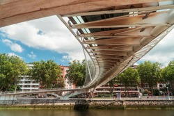 Zubizuri Bridge Structure Bilbao River. Dramatic Pattern underneath white bridge with leading lines. Famous Architecture steel suspension construction walkway. Puente Zubizuri Espana. River water.