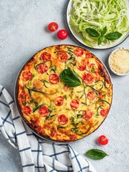 Zucchini pie and ingredients on gray background. Top view of delicious savory pie with zucchini, tomatoes, herbs and cheese. Idea and recipe for healthy baking and lot to harvest of zucchini. Vertical