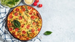 Zucchini pie on gray background, copy space right. Top view of delicious savory pie with zucchini, tomatoes, herbs and cheese. Idea and recipe for healthy baking and lot to harvest of zucchini