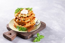 Zucchini waffle, zucchini fritters cooking on waffle maker, vegetarian zucchini waffles with basil on a plate. Copy space