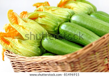 Zucchini with flowers in a basket on a white background