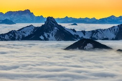 Zugspitze alps mountains foggy landscapes mountin sea of clouds mist bavaria germany nature landscapes at sunrise colored sky. Winter snow.