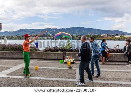 ZURICH, SWITZERLAND - SEP 21, 2014: A person entertain the crowd gathered at lake of Zurich. Outdoor entertainment is the part of European culture.