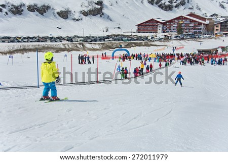 ZURS, AUSTRIA - APRIL 10, 2015: Kids skiing in a the Zurs - Lech, Arlberg, ski school. Parents and spectators are watching the kids racing on the final school day.  Conveyor is used to go up the hill.
