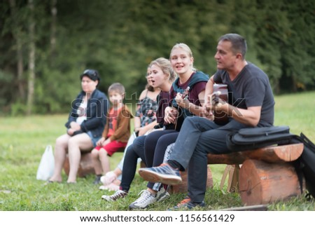 Zvenigorod, Russia, 15 AUG 2018. Group of happy friends with guitar in a central city park having fun outdoor. Camping couple. Adventure concept. Happy day. Musical concept. #1156561429