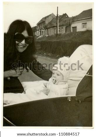 ZVOLEN, CZECHOSLOVAK REPUBLIC, CIRCA 1973 - young mother and her baby - circa 1973 - stock photo