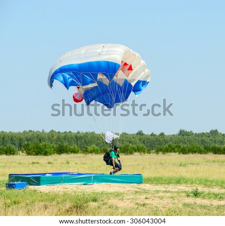 ZYABROVKA, BELARUS - AUGUST 8, 2015: Unknown woman -  skydiver completes a jump landing on the accuracy