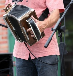 Zydeco accordion musician performing in concert outdoors.