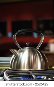 A stock photograph of a stainless steel tea kettle on a flaming gas stove.
