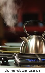A stock photograph of a steaming stainless steel tea kettle on a flaming gas stove.