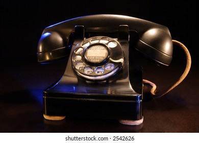 A stock photograph of a vintage black rotary telephone from the 1940's era.
