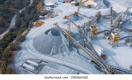 Stock pile and conveyors sorting gravel at stone quarry, aerial view