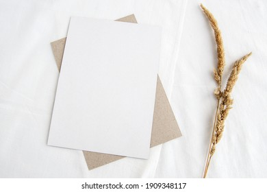 Escena de simulación de papel en una llave ligera. Tarjeta de saludo vertical vacía y hierba seca sobre fondo de lino blanco. Delicada vida quieta, vista superior.