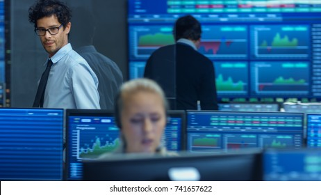 Stock Trader Goes Out of Office and Inspects Office. Busy Office with Multi-Ethnic Team of Brokers, Dealers. Displays Show Numbers and Infographics.
