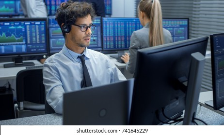 Stock Trader Making Sales with a Headset. In the Background Stock Exchange Office and Group of Traders Working at their Workstations.