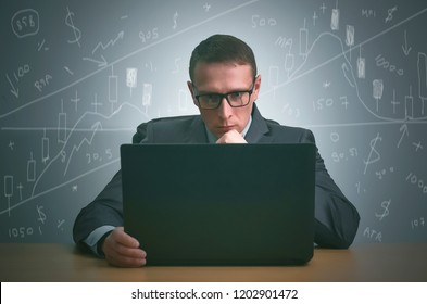 Stock trader is sitting by the table and is working on the laptop on the stock market. Technical analysis.