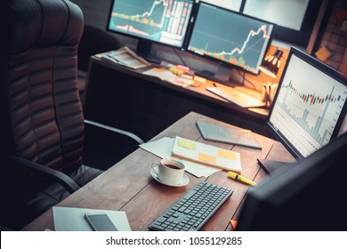 Stock trader workplace with financial market graphs on computer monitors