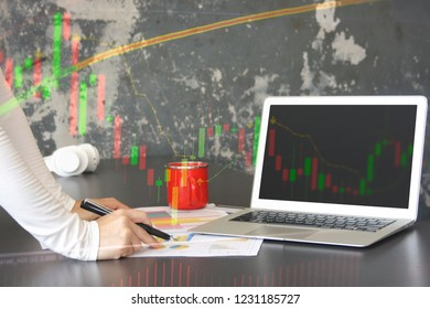 Stock traders are analyzing stock charts. Have laptops and desk documents, stock charts, picture techniques, picture overlays.