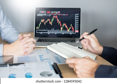 Stock traders looking at finance analysis marketing report trading stocks online in office