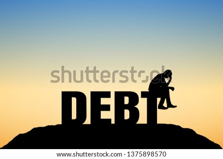 """Silhouettes of people sitting on the text """"DEBT"""" are worrying, not happy. sky and sunset background."""