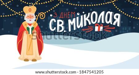 З Днем Св.Миколая. Translate:' Happy Saint Nicholas Day'. St. Nicolas holding gift in the winter city with hand drawn greeting lettering in Ukrainian language.  Foto d'archivio ©