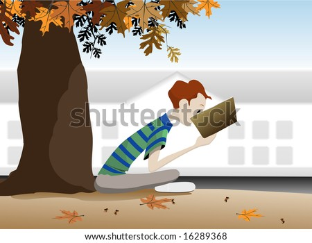 A boy reading a book under a tree in autumn.
