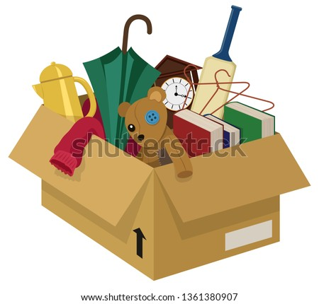 A cardboard box filled with various household junk items stock photo