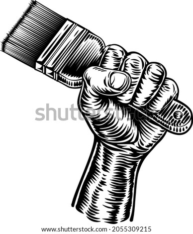 A fist hand holding a decorators paintbrush in a vintage intaglio woodcut engraved or retro propaganda style Stockfoto ©