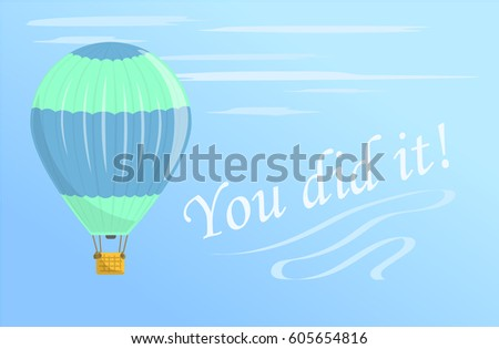 A green and blue hot air balloon flies in the sky. Flies in aerostat #605654816