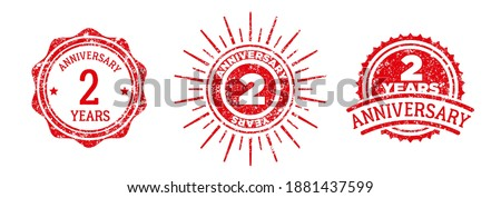 A group of 2 years anniversary logos drawn in the form of stamps, red frames for celebration. Grunge rubber stamp texture. Holiday stamps. Collection of postage stamps. Vector round stamps