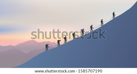 A roster of experienced alpinists climb the snowy slopes of a mountain to reach the summit. On the horizon the sun sets on the fairy landscape. Сток-фото ©