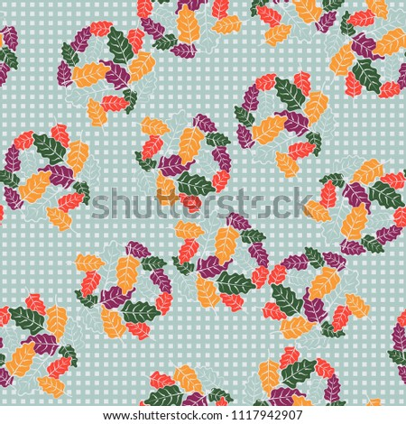 A seamless pattern consisting of groups of multicolored oak leaves. The background of the picture is a network consisting of small squares lined with the right rows.