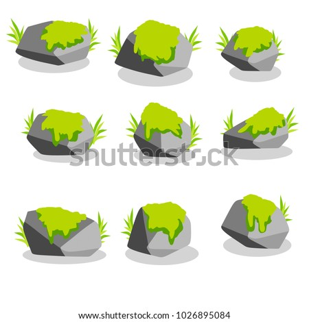 a set of gray granite stones of the cliff. rock for decoration. element of nature mountains with plants. green grass in the background. forest soft moss