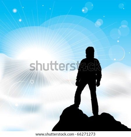 A silhouette of man staying on a top of a mountain and sun rays