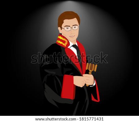 A standing judge, wearing his robe and holding a gavel in front of a black background. / Cübbesini giymiş ve siyah bir arka planın önünde, tokmak tutarak ayakta duran bir yargıç (hakim). Stok fotoğraf ©
