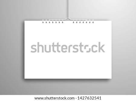 A white blank calendar or notebook on a spiral hangs on a thread near the wall. Realistic mockup for design