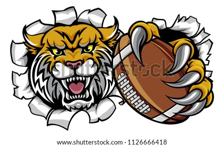 A wildcat angry animal sports mascot holding an American football ball and breaking through the background with its claws