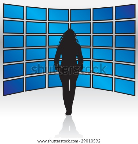 A woman standing in front of a wall of widescreen LCD or plasma TV screens.